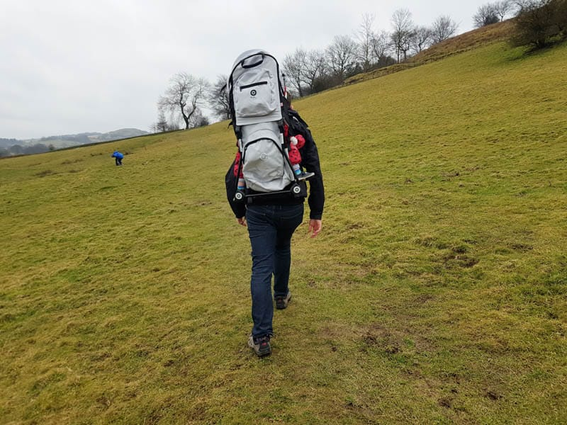 Man climbing hill with toddler in Kiddy Adventure pack on his back.