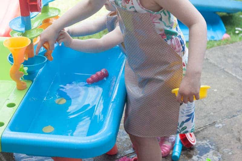 Child wearing messy me oilcloth apron playing in water table