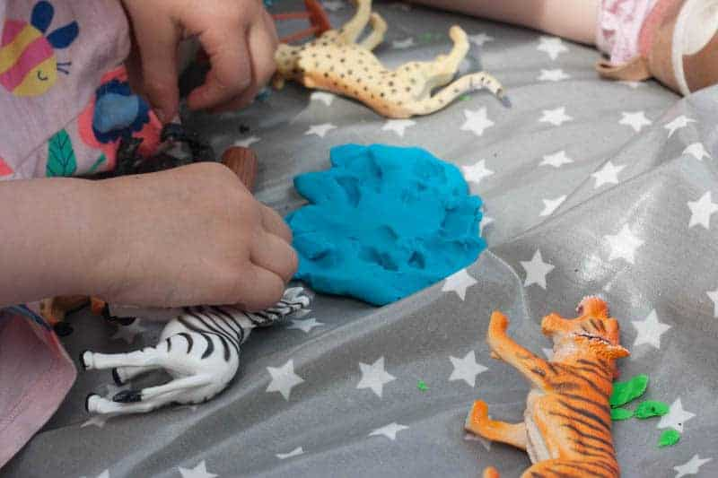 Play dough and plastic animals on messy me oilcloth