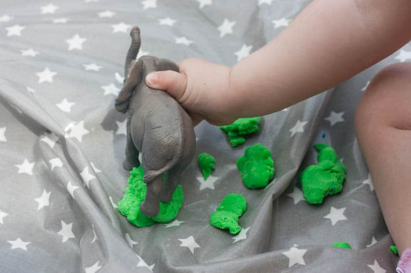 Toddler's hand and plastic elephant with play dough on messy me oilcloth