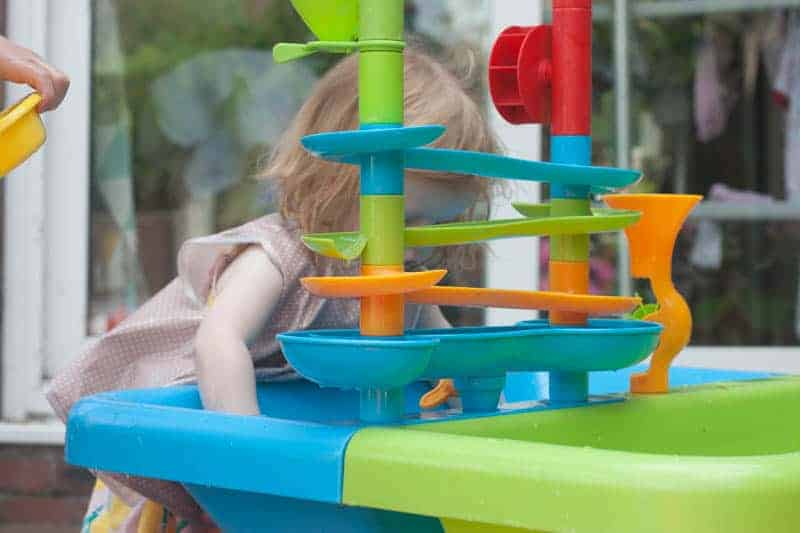 Toddler playing in colourful water table wearing messy me apron