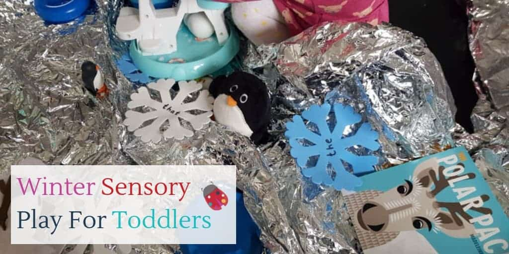 Toddler playing with silver foil, foam snowflakes and penguin toys