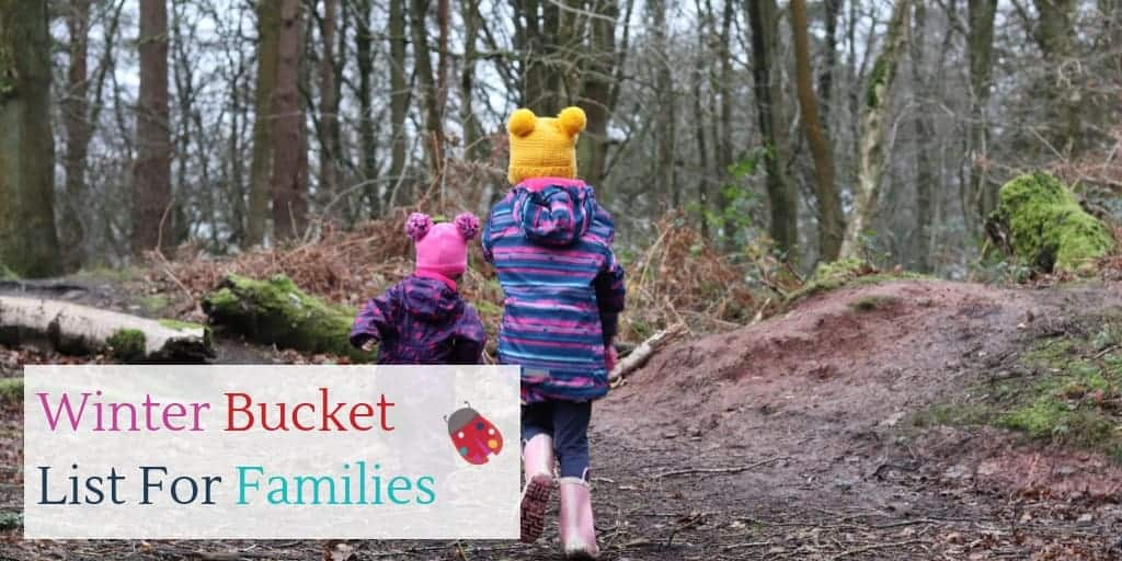 2 children, dressed for winter, running in the woods