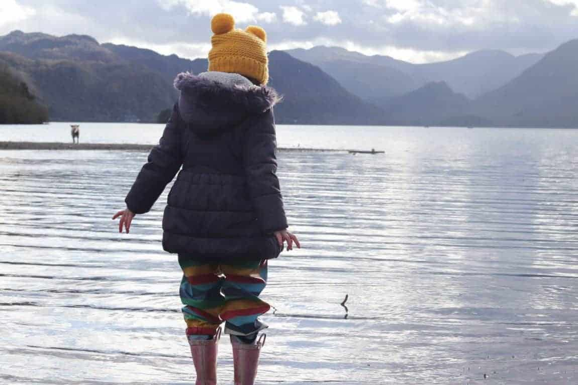 Girl in winter clothing and wellies paddling in a lake